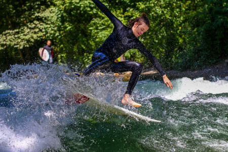 Munich, Germany - July 13, 2019: Surfer in the city river, Munich is famous for people surfing in urban enviroment called Eisbach Editorial