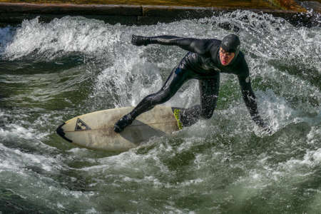 Munich, Germany - December 13, 2018: Surfer in the city river, Munich is famous for people surfing in urban enviroment called Eisbach Redactioneel