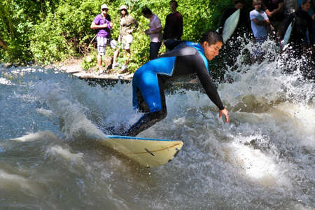 Munich, Germany - July 13, 2019: Surfer in the city river, Munich is famous for people surfing in urban enviroment called Eisbach Redactioneel