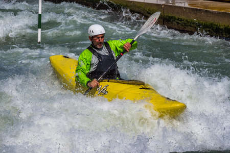 Augsburg, Germany - June 16, 2019: Whitewater kayaking, extreme kayaking. A guy in a kayak sails on the Eiskanal in Augsburg Germany