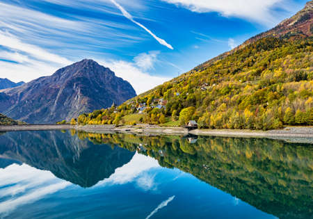The lower reservoir of Lac du Verney at Allemond in France. It is the largest hydroelectric power station in France. The waters of the lake mirror the mountain ranges surrounding the Eau d Olle valley