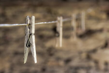 Old wooden clothes pegs on cord with stone wall on background