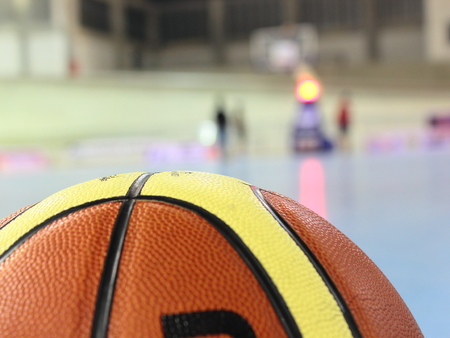 game over: Basketball on Court Floor close up with blurred arena in background Stock Photo
