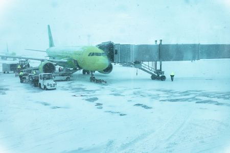 Maintenance of green transport aircraft in snowy weather. beautiful green passenger plane in a blizzard. aircraft preparation at the airport