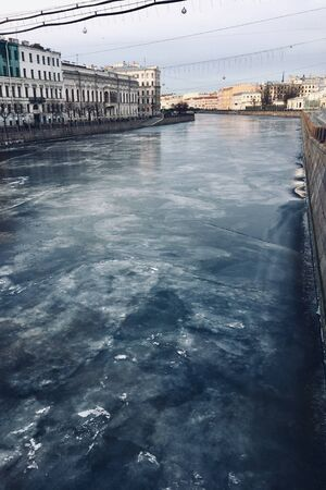 Frozen Neva in Petersburg. icy blue river on the background of a beautiful historic buildings. cloudy weather in winter near the river. vertical image