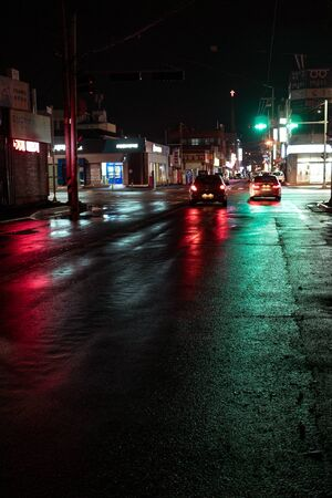 Seoul, South Korea - 30.10.18: two cars drive along the road at night. green light of the traffic light is reflected on the wet asphalt. beautiful neon lights at night