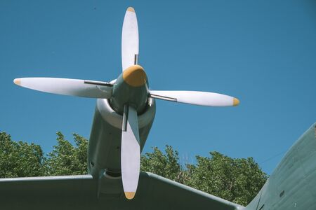 white propeller of an old military aircraft close-up. big white propeller on the wing of a green airplane against a blue sky