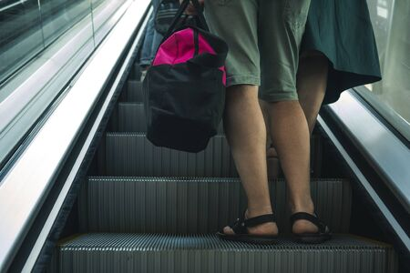 a man with a bag on a trip is understood on the escalator. a man holding a pink bag and riding an escalator. man collected things and flies off on leave at the airport