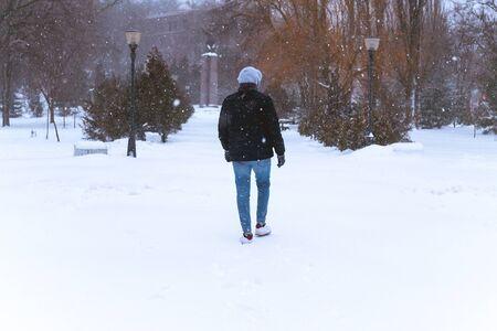 l'uomo cammina da solo in inverno nel parco. l'uomo solitario va tra la neve e gli alberi