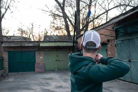 young guy in a white baseball cap shoots a bow. archer is training on the street. a man stands with his back to the camera and shoots a bow. Imagens