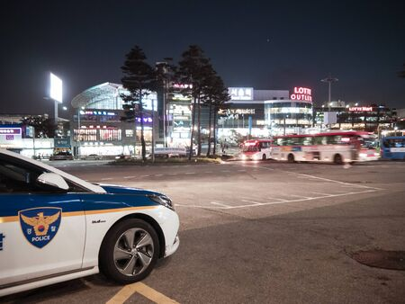 Seoul, South Korea - 08.05.18: a police car is on duty at night. police car parked on a busy street in the evening. policing on the highway. police are on duty in the night city