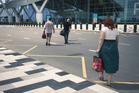 Airport Platov, Russia - 24.05.19: beautiful adult woman with red hair goes with the family to the airport. a woman in a white T-shirt and a green skirt crosses the road before entering the aeroport