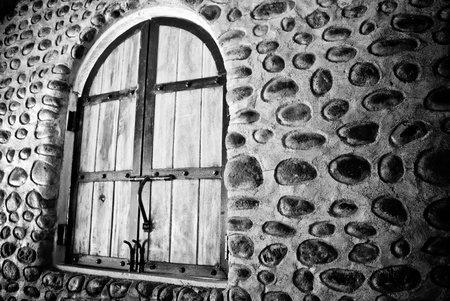 A haunting black and white photo of an old rustic stone wall and vintage farm-style arched windows.