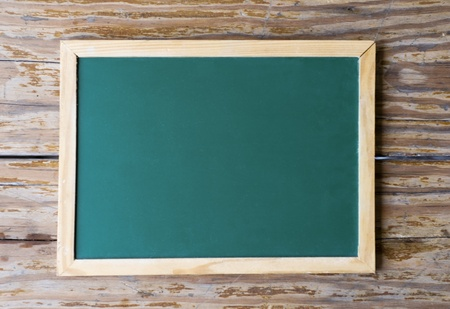 Green blackboard on a background of old, weathered wood.