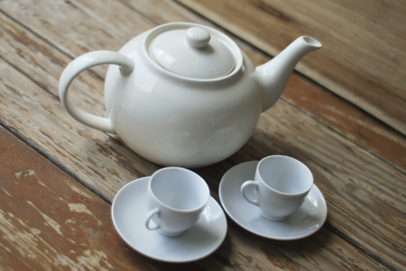Traditional teapot and two cups set on a wooden table photo