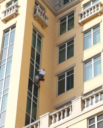 Man hanging on a rig to clean windows Stock Photo