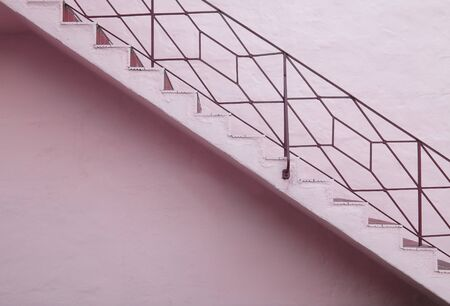 upward struggle: Lilac staircase with iron railing on lilac wall