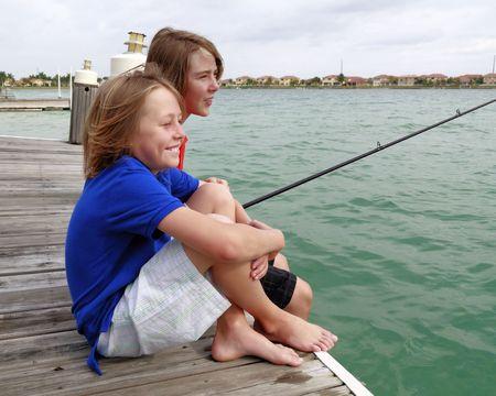 Two brothers fishing in an urban lake