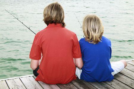 Two brothers fishing in an urban lake Фото со стока - 4674279