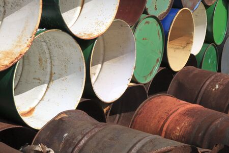 Background of colorful old rusty abandoned metal barrels Stock Photo