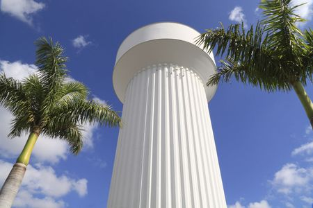 Modern water tower with palm trees against a clear blue sky