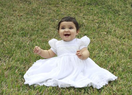 Portrait of a little toddler sitting in the grass having a good time in a baptismal gown