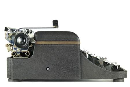 Oldalnézetből egy fekete kopott vintage írógép fehér alapon