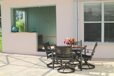 Beautiful residential screened-in patio with furniture and a bar