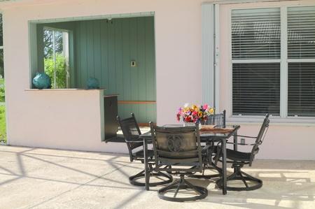 Szép lakás árnyékolt udvarán bútorok és egy bár Stock fotó