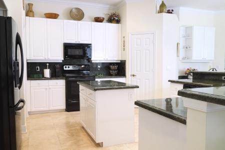 Kilátás egy szép modern konyha előkelő készülékek, fehér szekrények, és zöld gránit munkalapok