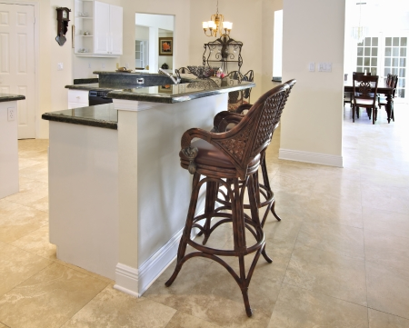 View of a beautiful modern kitchen bar with green granite counter tops and white cabinets photo
