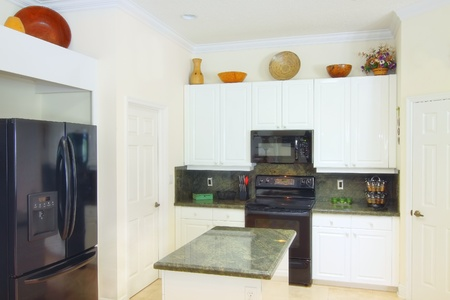 View of a beautiful modern kitchen with upscale appliances, white cabinets, and green granite countertops photo