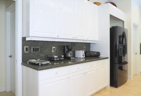 Nézd meg a szép modern konyha előkelő készülékek, fehér szekrények, és zöld gránit munkalapok
