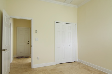 View of an empty room with closet and doorway photo