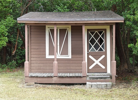 Rustic wooden shed with window and front porch at the edge of the forest photo