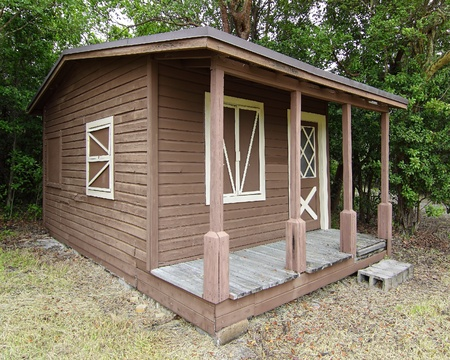 front porch: Cobertizo de madera r�stica con ventana y porche delantero en el borde de la selva