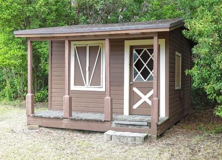 ウィンドウとフロント ポーチの森林の端で素朴な木製小屋