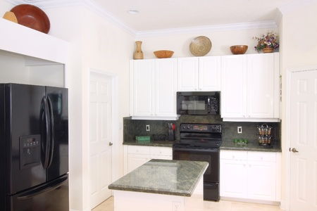 stone worktop: View of a beautiful modern kitchen with upscale appliances, white cabinets, and green granite countertops
