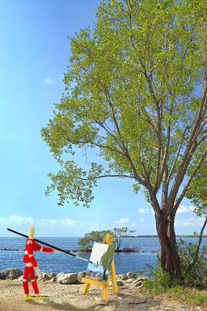Wooden mannequin with an easel painting a landscape Stock Photo - 12408776