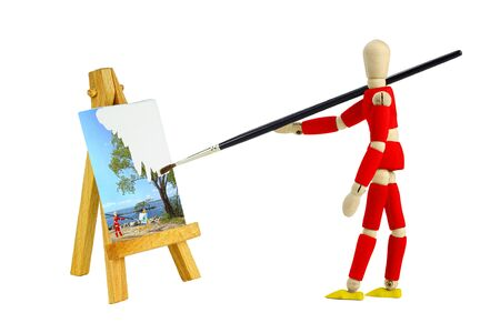 wooden mannequin: Wooden mannequin with an easel painting a landscape, isolated on white