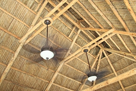 fan ceiling: Ceiling rafters of a hand build tiki hut with ceiling fans Stock Photo