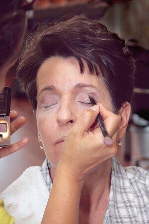 Applying make-up on a middle aged Hispanic female Stock Photo - 13225889