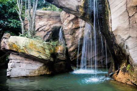 View of a beautiful relaxing tropical waterfall pouring down in a small lake formed out of limestone