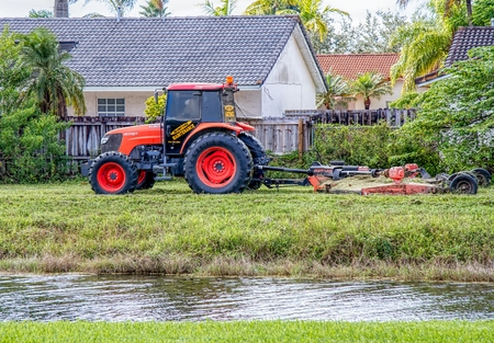 Commercial tractor type lawn mower at work in a residential area Фото со стока - 34431549