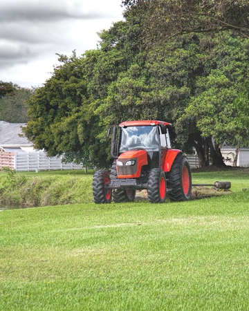 Commercial tractor type lawn mower at work in a residential area Фото со стока