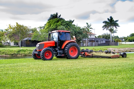 Commercial tractor type lawn mower at work in a residential area Banco de Imagens