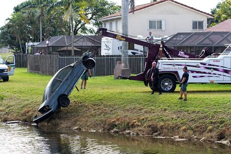 MIAMI, FLORIDA - DECEMBER 14, 2014: A Miami-Dade County Sheriff Departments Diving team retrieves a completely stripped and suspicious looking car from a canal in a residential neighborhood Editorial