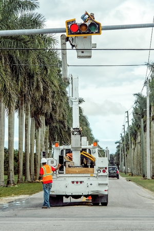MIAMI, FLORIDA - January 13, 2015: Electrical workers are busy repairing a broken traffic light on a busy intersection.