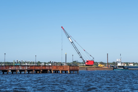 Floating crane working on the repair of a floating dock for the local marina Фото со стока - 37363727