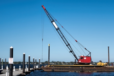 Floating crane working on the repair of a floating dock for the local marina Фото со стока